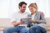 Pareja feliz usando un equipo tablet pc — Foto de Stock