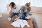 Depressed couple doing their accounting — Stockfoto