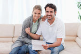 Delighted couple reading a letter — Stock Photo