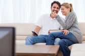 Lovely couple watching TV while eating popcorn — Stock Photo