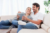 Delighted couple using a tablet computer — Stock Photo