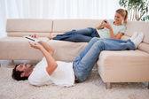 Onun erkek arkadaşı bir tablet kullanırken onun akıllı telefon kullanan kadın — Stok fotoğraf