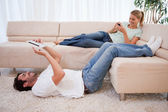 Vrouw met behulp van haar smartphone terwijl haar vriendje is met behulp van een tablet pc — Stockfoto