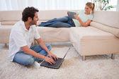 Vrouw met behulp van een tablet-computer terwijl haar verloofde is met behulp van een laptop — Stockfoto