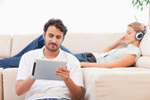 Man using a tablet computer while his girlfriend is listening to — Stock Photo