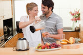 Young couple making fresh fruits juice — Stock Photo