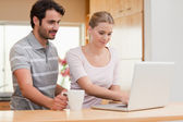 Couple using a laptop while having coffee — Stock Photo