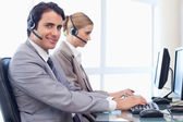 Smiling operators using a computer — Stock Photo