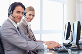 Good looking operators using a computer — Stock Photo
