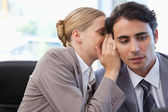 Businesswoman whispering something to her colleague — Stock Photo