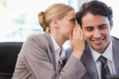 Young businesswoman whispering something to her colleague — Stock Photo
