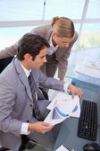 Portrait of a manager and his secretary looking at a graph — Stock Photo