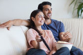 Couple watching TV while eating popcorn — Stock Photo