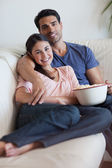 Portrait of a smiling couple watching television while eating po — Stock Photo