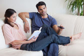 Woman reading a book while her fiance is watching television — Stock Photo