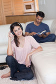Portrait of a young woman listening to music while her fiance is — Stock Photo