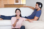 Woman watching television while her husband is listening to musi — Stock Photo