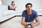 Man playing video games while his fiance is getting mad at him — Stock Photo