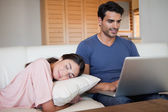 Man using a laptop while his fiance is sleeping — Stock Photo