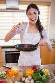 Portrait of a happy woman preparing a dish — Stock Photo