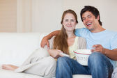 Smiling couple watching television while eating popcorn — Stock Photo