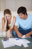Portrait of a worried couple looking at their bills — Stock Photo