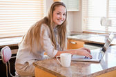 Woman having coffee while using a laptop — Stock Photo