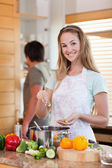 Portrait of a woman cooking while her fiance is washing the dish — Stock Photo