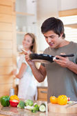 Portrait of a man cooking while his fiance is washing the dishes — Stock Photo