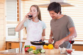 Couple cooking dinner while drinking wine — Stock Photo