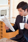 Portrait of a businessman drinking tea while reading the news — Stock Photo
