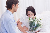 Man brought flowers to his girlfriend in the hospital — Stock Photo