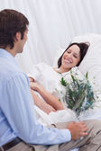Woman is happy about receiving a visit at the hospital — Stock Photo