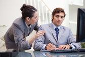 Empresario tomando notas mientras recibe explicación por colega — Foto de Stock
