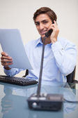 Smiling businessman holding paperwork while on the phone — Stock Photo