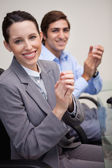Side view of business team clapping while sitting at desk — Stock Photo