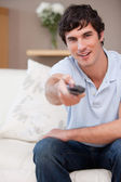 Man on the sofa switching on television — Stock Photo