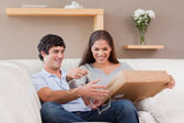 Couple opening parcel on the couch — Stock Photo