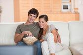 Coppia con popcorn sul divano guardando un film — Foto Stock