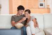 Couple on the couch watching a movie together — Stock Photo