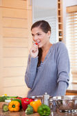 Woman snacking a small tomato while preparing dinner — Stock Photo