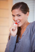 Woman snacking a small tomato — Stock Photo