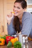 Donna sorridente mangiare un peperone in cucina — Foto Stock