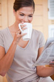 Woman taking a sip of coffee while reading newspaper — Stock Photo