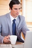 Businessman with coffee on his laptop — Stock Photo