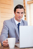 Businessman with laptop and tea — Stock Photo