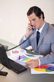 Businessman on the phone talking about statistics — Stock Photo