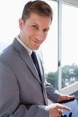 Businessman with his tablet in front of the window — Stock Photo