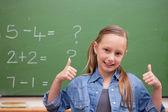 Lachende schoolmeisje met de duimen omhoog — Stockfoto