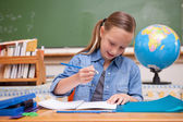 Smiling schoolgirl doing classwork — Stock Photo